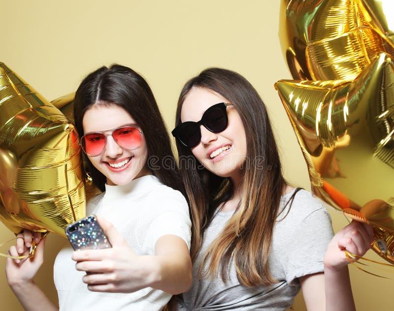 Två vänner för tonårs- flickor med guld- ballonger gör selfie på ett p arkivfoto
