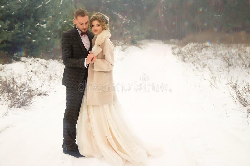 Två vänner i skogen, ett lyckligt par och att krama som kräver leende, brud och brudgum Gifta sig i vinter dräkt och bröllopsklän royaltyfria bilder