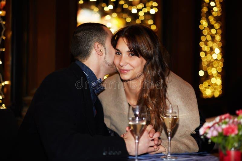 Två vänner sitter i en restaurangman som sött viskar ord i örat av flickan royaltyfria bilder