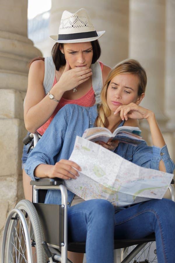 Två vänner som besöker utländsk stad en som sitter i rullstol royaltyfria foton