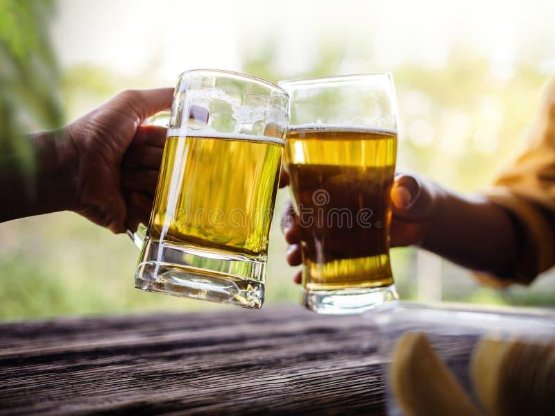 Två vänner som gör jubel med exponeringsglas och dricker öl arkivfoto