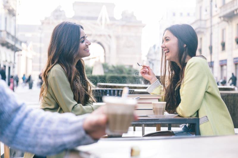 Två vänner som har ett kaffe i centret royaltyfria foton