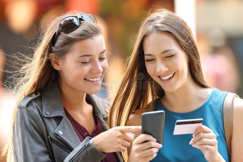 Två vänner som köper på linje på gatan royaltyfri foto