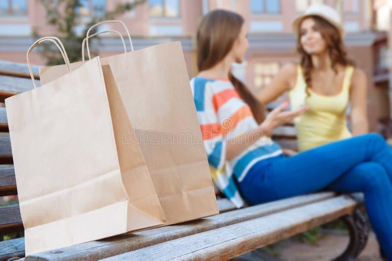 Två vänner som kopplar av på en bänk under shopping royaltyfri fotografi