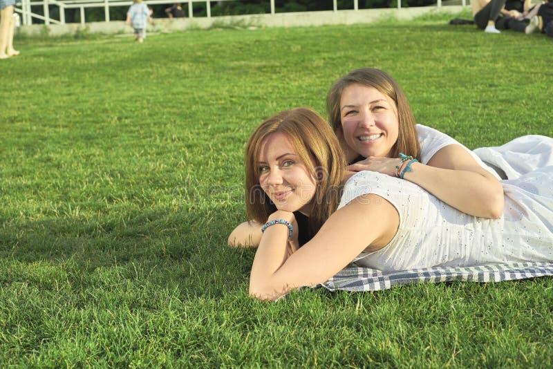 Två vänner som ligger på gräsmattan arkivbilder