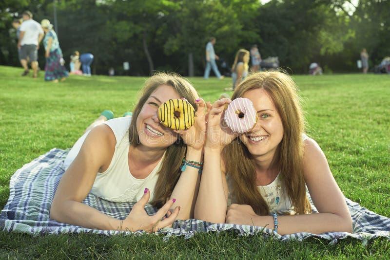 Två vänner som ligger på gräsmattan royaltyfri fotografi