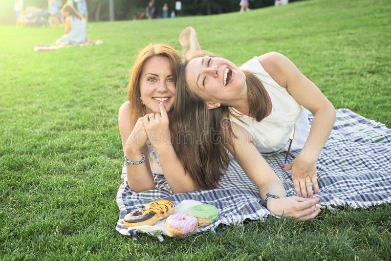 Två vänner som ligger på gräsmattan fotografering för bildbyråer