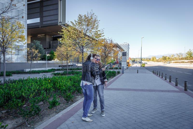 Två vänner som lyssnar till musik och ser skärmen av en mobiltelefon, i mitt av en gata royaltyfria bilder