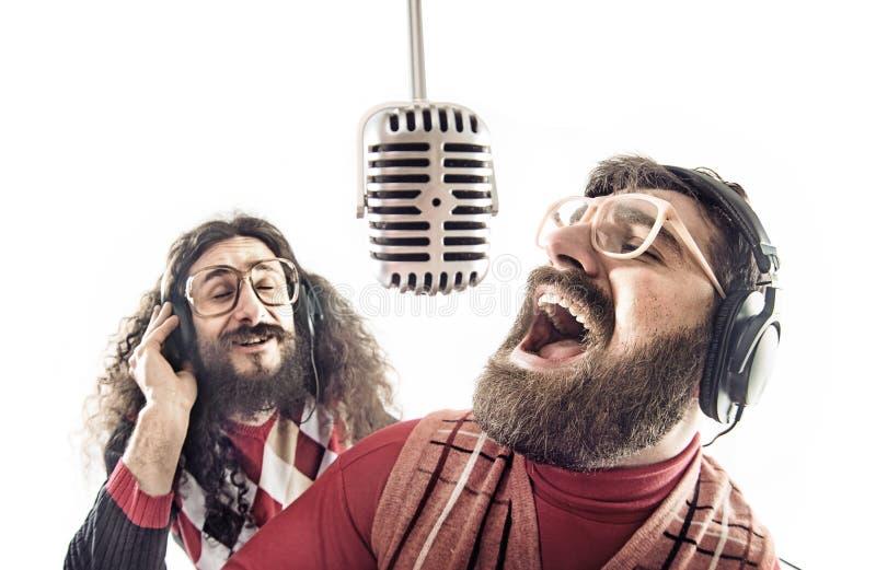Två vänner som sjunger en karaoke royaltyfri foto