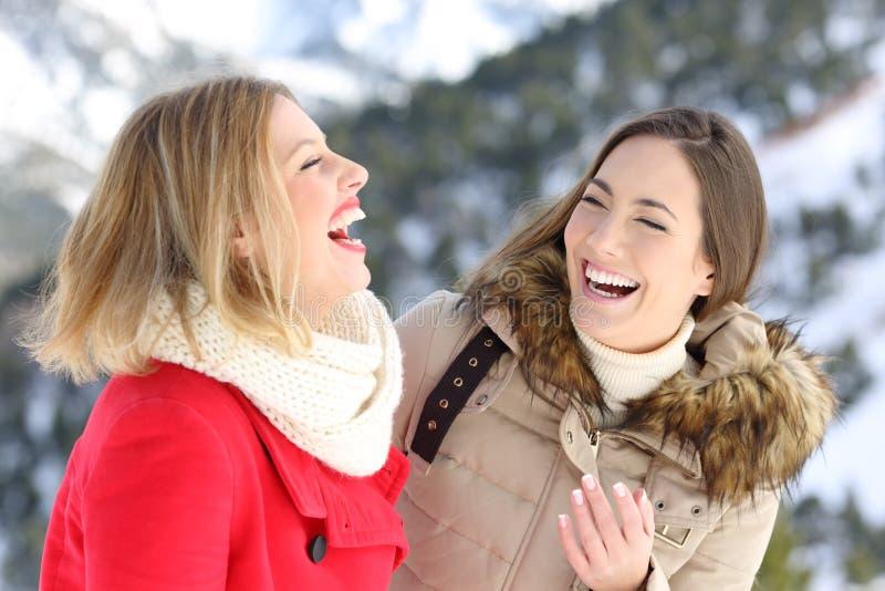 Två vänner som skrattar i vinterferier arkivbild
