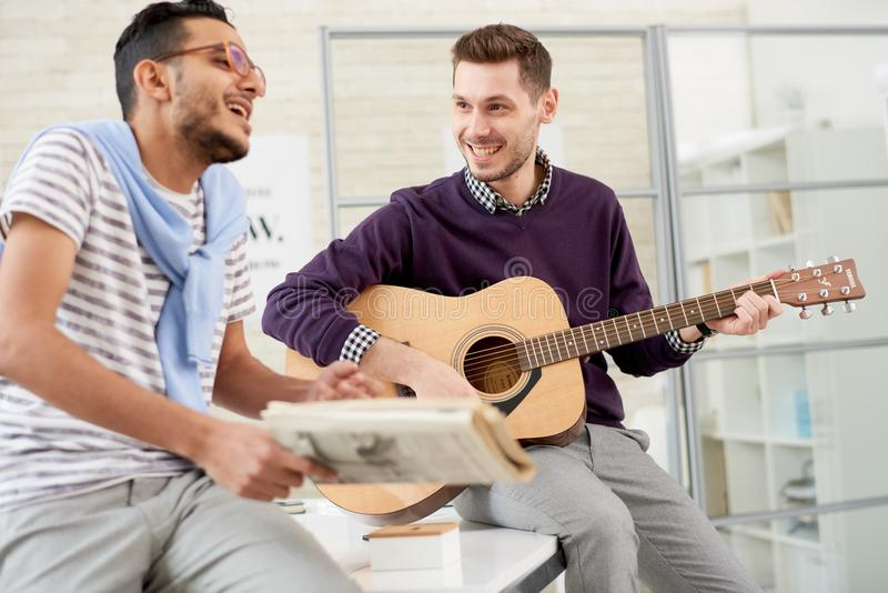 Två vänner som spelar gitarren royaltyfria foton