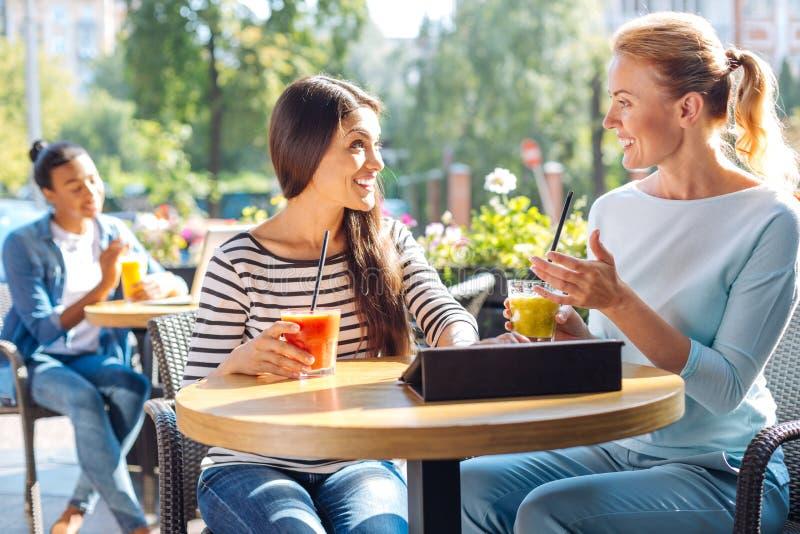 Två vänner som talar och dricker smoothien i kafé arkivbild