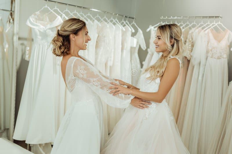 Två vänner som tillsammans försöker på bröllopsklänningar royaltyfria foton