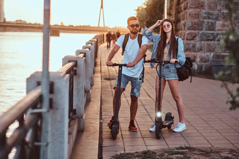 Två vänner tycker om sommardag med deras electro sparkcyklar arkivfoto