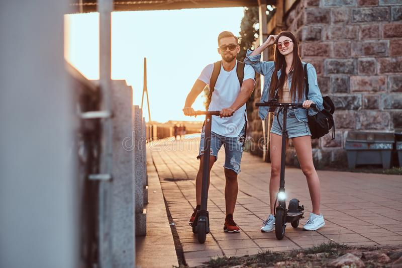 Två vänner tycker om sommardag med deras electro sparkcyklar royaltyfri bild
