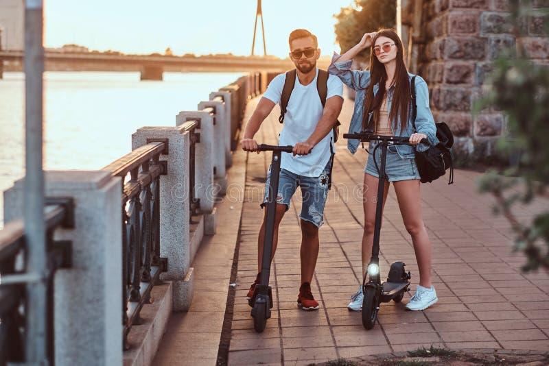 Två vänner tycker om sommardag med deras electro sparkcyklar arkivfoton