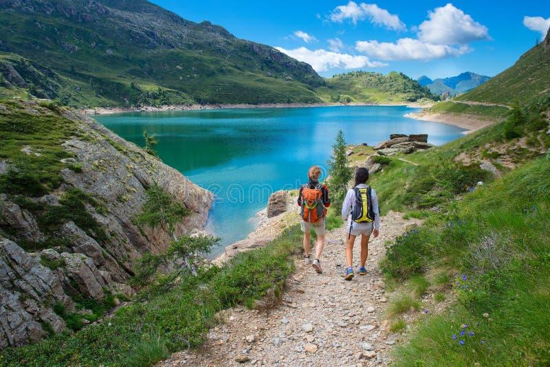 Två vänner under en vandring i bergen som går nära en alpin fotografering för bildbyråer