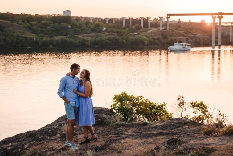 Två vänpersoner på solnedgången vid floden royaltyfri fotografi