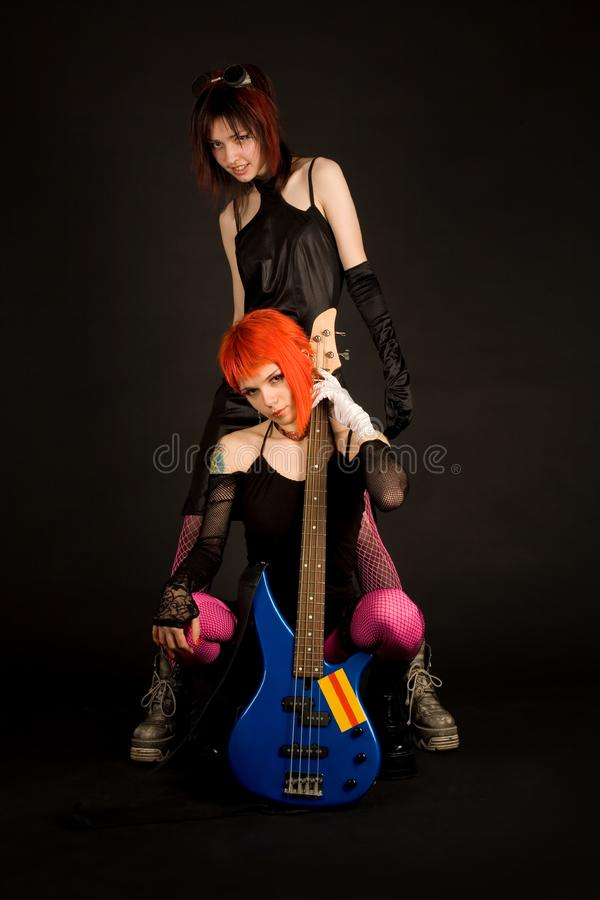 Två vaggar flickor med gitarren royaltyfria bilder