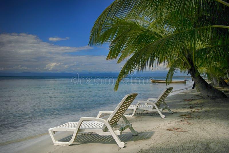 Två vara slö stolar på stranden royaltyfri fotografi