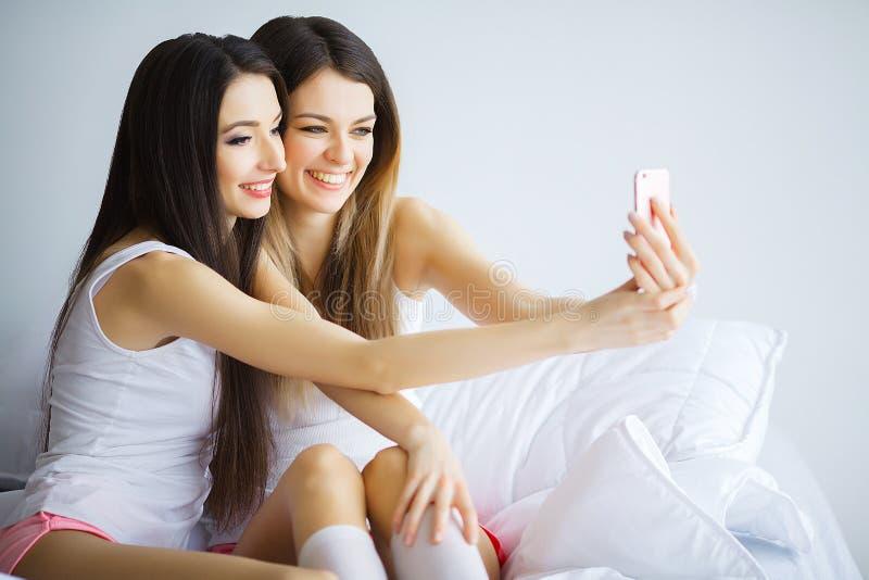 Två varma flickor som ligger på en säng som tar ett foto av dem fotografering för bildbyråer