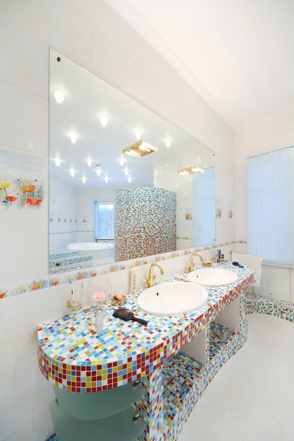 Två vaskar och stor spegel i rymligt badrum arkivbild