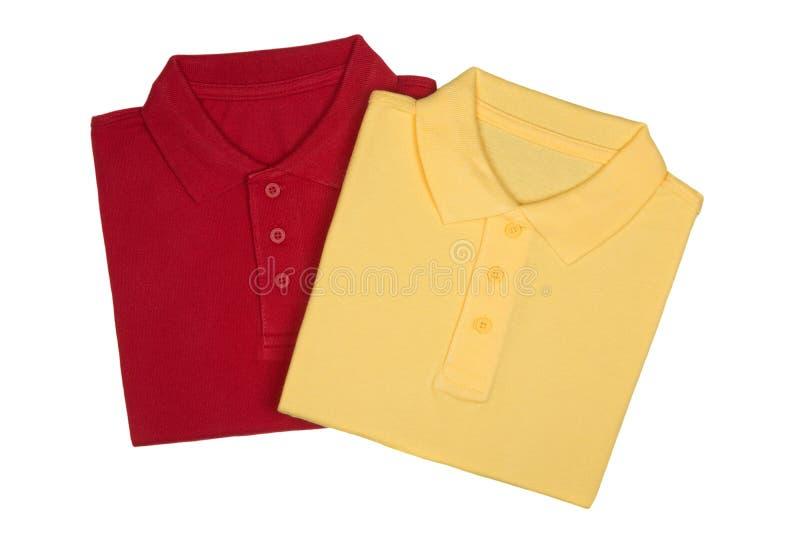 Två vek röda och gula poloskjortor som isolerades på vit royaltyfri foto