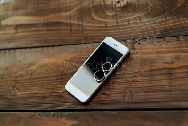 Två vigselringar lägger på en vit telefon på tabellen Guld- cirklar köptes för bröllopet arkivfoto