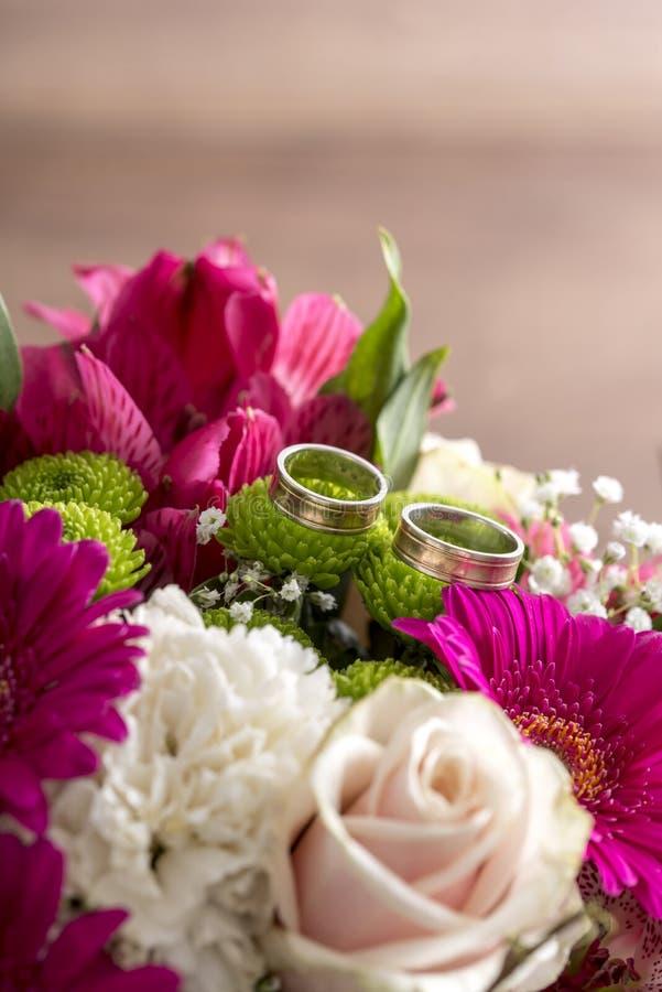 Två vigselringar på blommor av en brud- färgrik bukett royaltyfri foto