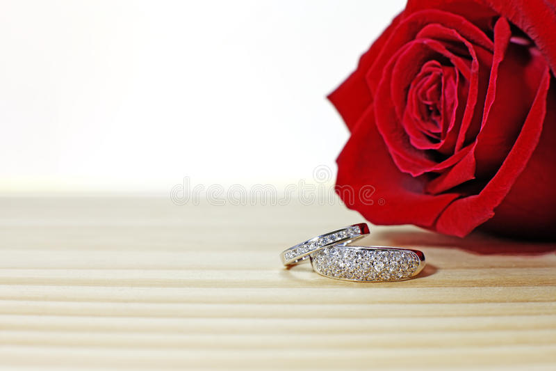 Två vigselringar på trätabellen med mörker - röd ros royaltyfri fotografi