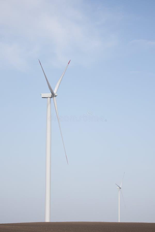 Två vindturbiner på jordbruks- jordning med klar himmel i bakgrund royaltyfri foto