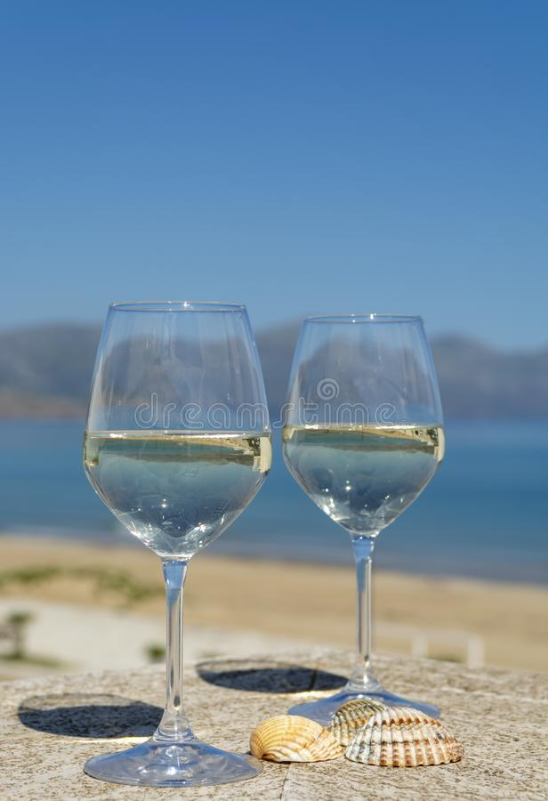 Två vinexponeringsglas med vitt vin som tjänas som på sikt för hav och för berg för utomhus- terrasswitn blå på bakgrund fotografering för bildbyråer