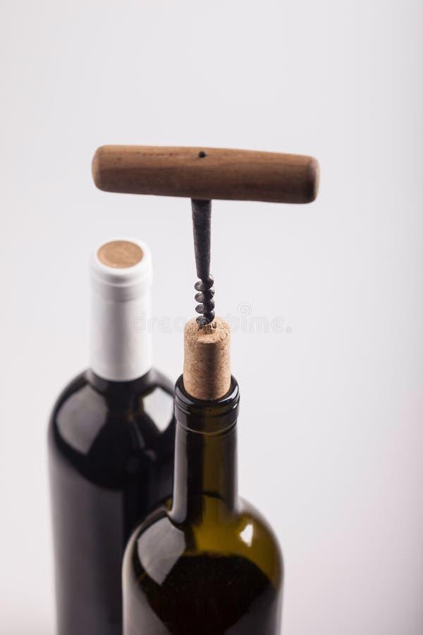 Två vinflaskor, kork och korkskruv på vit bakgrund royaltyfri fotografi