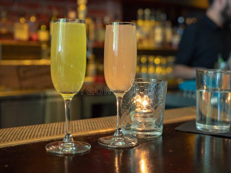 Två vinglas som fylls med mimosan, dricker sammanträde på en stångräkning royaltyfri bild