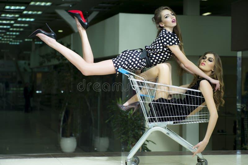 Två vinnande flickor i shoppingspårvagn fotografering för bildbyråer