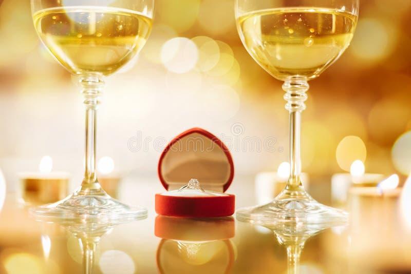 Två vinvinglas och den röda asken med förlovningsringen över bokehbakgrund royaltyfri fotografi