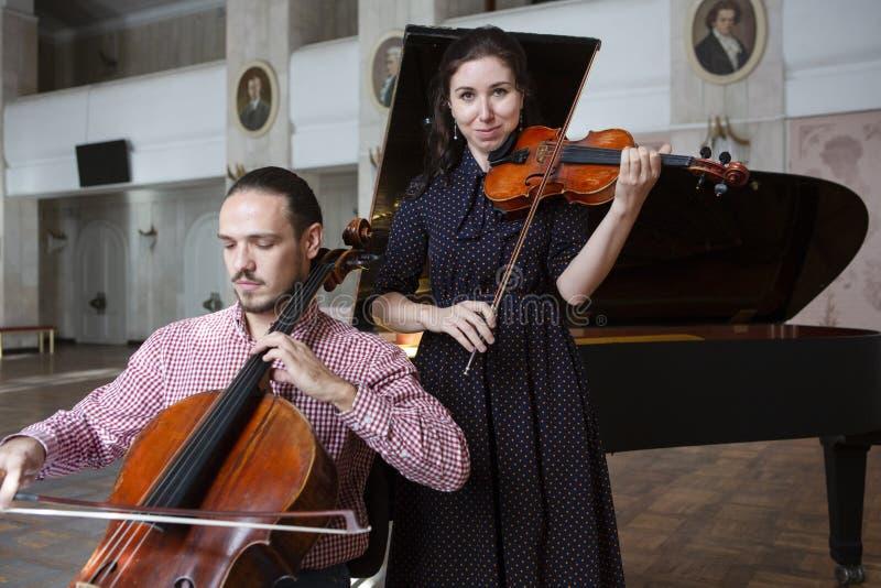 Två violinister som tillsammans utför, räcker tätt upp royaltyfria bilder