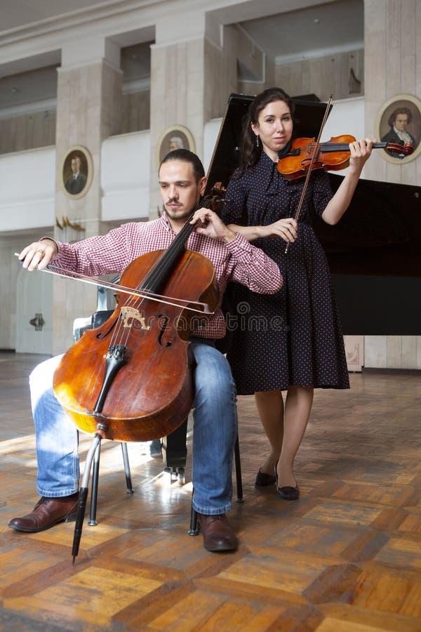 Två violinister som tillsammans utför, räcker tätt upp arkivbild
