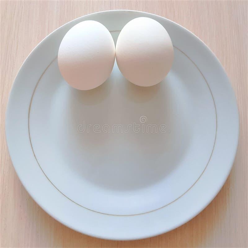 Två vita ägg på en platta, ser som en framsida med ett leende arkivbilder