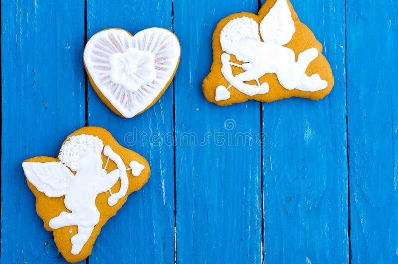 Två vita änglar och en hjärta Ljust rödbrun kex i chokladglasyr valentin för dag s Lekmanna- lägenhet arkivfoto