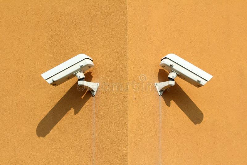 Två vita bevakningkameror med den starka metallcasingen som monteras på industriellt komplext byggande hörn royaltyfri fotografi