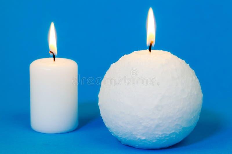 Två vita brinnande stearinljus på blått royaltyfria bilder