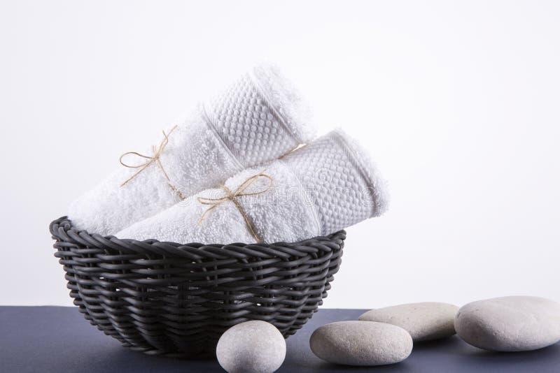 Två vita handdukar i en svart korg royaltyfri foto