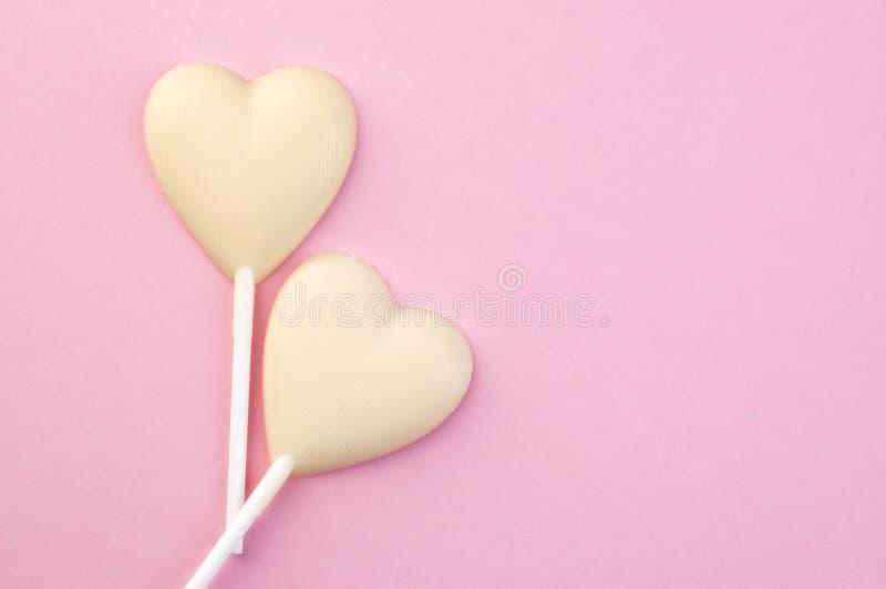 Två vita hjärtor för chokladgodis på rosa färger royaltyfri foto