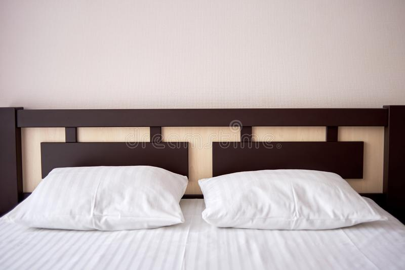 Två vita mjuka kuddar på säng med den bruna trähuvudgaveln i hotellsovruminre, kopieringsutrymme arkivbilder