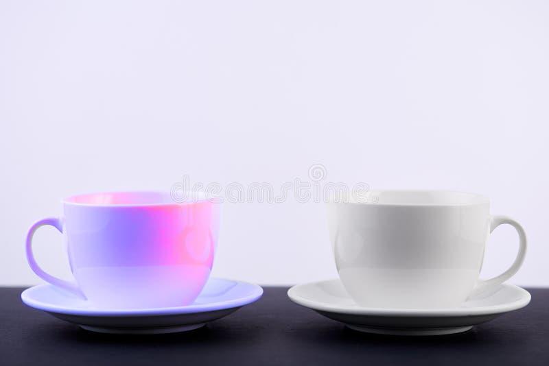 Två vita porslintekoppar på den svarta tabellen visar fullständigt och idéer för den enkla designen, selektiv fokus royaltyfri foto