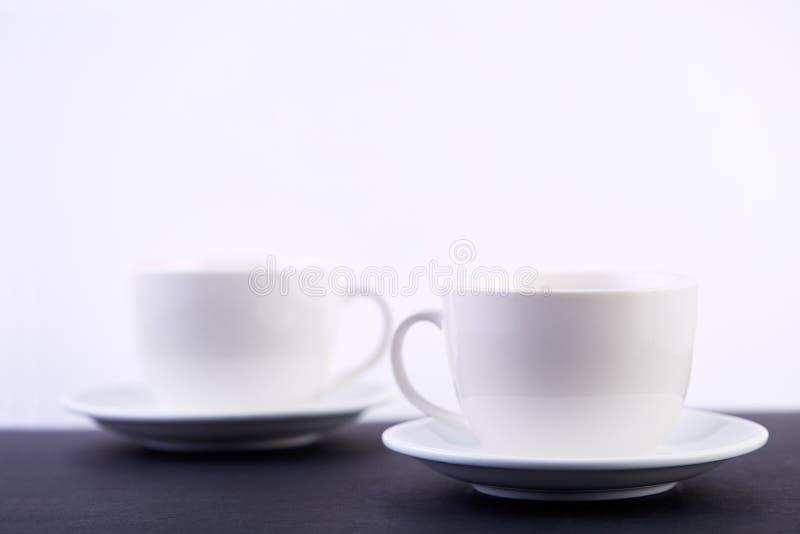 Två vita porslintekoppar på den svarta tabellen visar fullständigt och idéer för den enkla designen, selektiv fokus royaltyfri fotografi