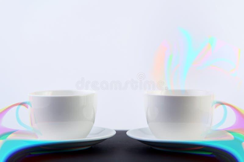 Två vita porslintekoppar på den svarta tabellen visar fullständigt och idéer för den enkla designen, selektiv fokus fotografering för bildbyråer