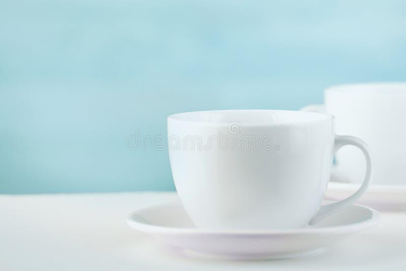 Två vita porslintekoppar på den vita tabellen visar fullständigt och idéer för den enkla designen, selektiv fokus arkivbild