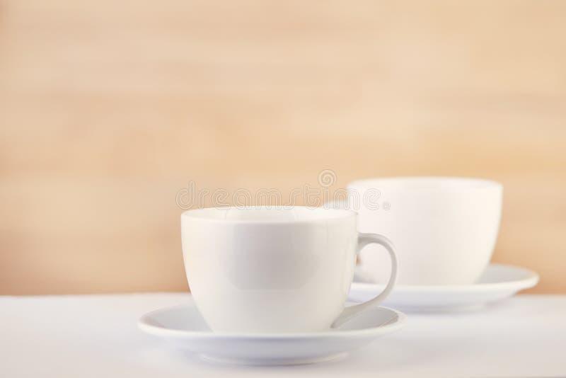 Två vita porslintekoppar på den vita tabellen visar fullständigt och idéer för den enkla designen, selektiv fokus royaltyfri bild